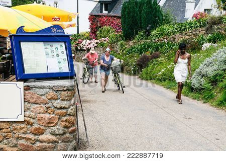 ILE-DE-BREHAT, FRANCE - JULY 4, 2010: tourists near restaurant on street in Brehat commune. Ile-de-Brehat is island and commune located near Paimpol town, a mile from the northern coast of Brittany