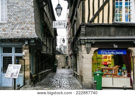 DINAN, FRANCE - JULY 5, 2010: old half-timbered houses on square Place des Merciers in Dinan city in rain. Dinan is a walled town and commune in the Cotes-d'Armor department of Brittany