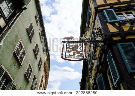 COLMAR, FRANCE - JULY 11, 2010: medieval urban houses and typical tavern sign board on street Rue des Serruriers Colmar city. Colmar is the third-largest commune of Alsace region.