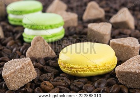 lemon yellow biscuit macaroni along with a pair of apple green biscuit macaroni lie on coffee grains with sugar hearts