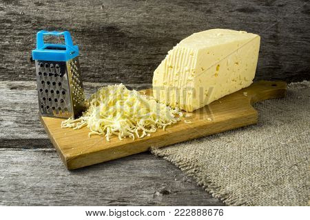 Grater and cheese on old wooden board