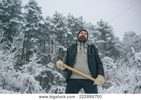 Bearded man with axe in snowy forest. Man lumberjack with ax. Temperature, freezing, cold snap, snowfall. skincare and beard care in winter, beard warm in winter. Camping, traveling and winter rest.
