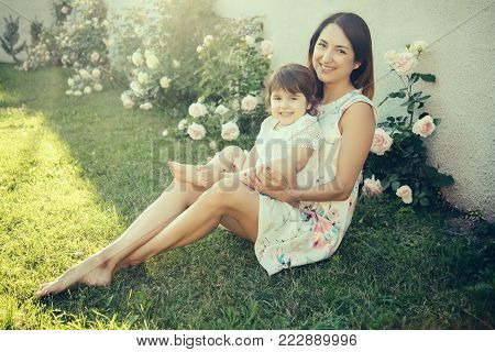 Woman with baby girl sitting on green grass. Mom and child smiling at blossoming rose flowers. Mothers day concept. Family love and care. Nurturing and future.