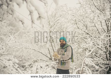 Winter sport and rest, Christmas. Bearded man with skates in snowy forest. skincare and beard care in winter. Man in thermal jacket, beard warm in winter. Temperature, freezing, cold snap, snowfall.