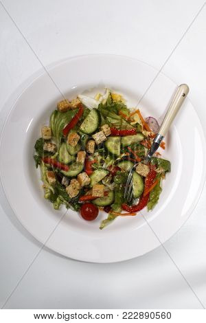 fresh cucumber salad with croutons and red bell pepper stripes on a white plate