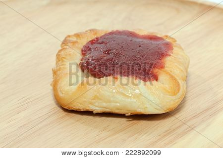 close up of strawberry danish on wooden plate