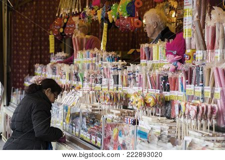 Leiden, The Netherlands 3 October 2017, a big candy fair vendor stand with a woman buying sweet candy