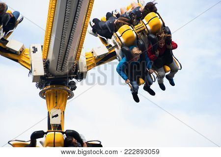 Leiden, The Netherlands 3 October 2017, children sitting in a fast spinning fair park attraction high up in the air