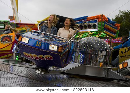 Leiden, The Netherlands 3 October 2017, two girls sitting in the seats of a fast spinning fair ground attraction ride.