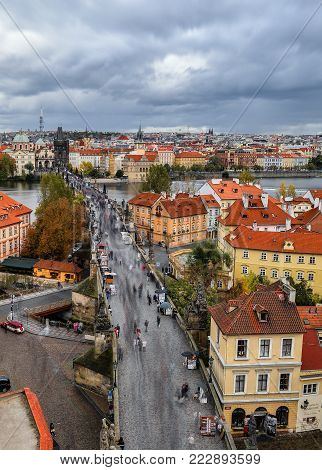 Prague, Czech Republic - October 7, 2017: Top aerial view on ancient Charles Bridge crosses Vltava river in Prague. Tourists are walking Charles Bridge and enjoying golden autumn and dramatic sky