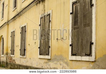 Wall of old building with window with  closed wooden shutters