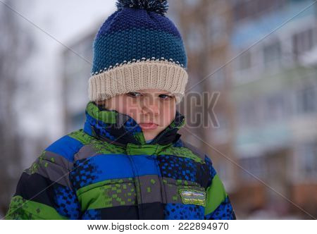 portrait of a European boy with a strong emotion of resentment on his face while walking in the winter