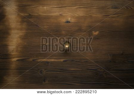 Small empty brass goblet on wooden table backgorund with copy space. Abstract background.