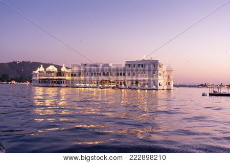 Jag nivas lake palace on lake pichola at dusk. This luxury hotel sits on an artifical island in the middle of the lake. It's a popular stay location for tourists to Udaipur Rajasthan India