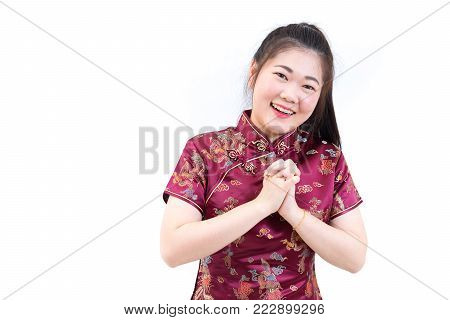 Portrait of asian woman in traditional chinese long dress, cheongsam, black hair, nice smile with greeting hands in Chinese style for Chinese New Year festival, celebration time, happy feeling