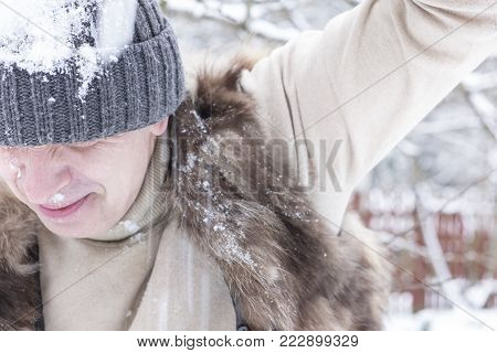 A man wearing wool hat getting a snowball hit in his head, outdoor emotional shot