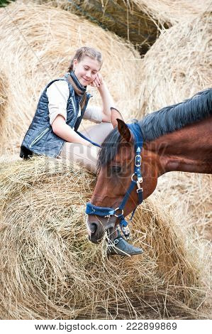 Pretty young teenage girl owner sitting on yellow hay/straw rolled stack and looking after her favorite bay horse at farm yard. Vibrant colored outdoors vertical summertime image.
