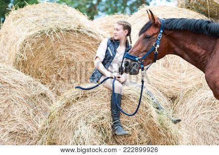 Pretty young teenage girl owner sitting on yellow hay/straw rolled stack near her favorite bay horse at farm yard. Vibrant colored outdoors horizontal summertime image.