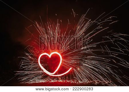 Red Heart Shaped Firework With Sparkles On Black Background In Night. Happy Valentine's Day Card. Be