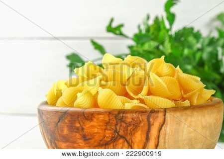 Culinary background with conchiglie pasta on wooden table. Pasta in the form of cockleshells in a wooden bowl with parsley