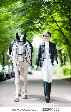 Young pretty cheerful teenage girl in dress uniform leads a white horse in green alley at equestrian school competition. Colored outdoors vertical summertime image.