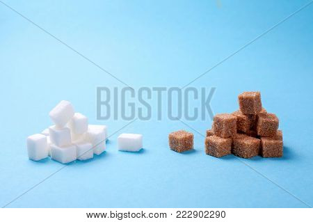Which sugar is more useful than white or brown. White and brown sugar cane sugar cubes on a blue background. Copy space for text