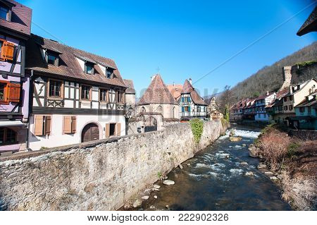 French traditional half-timbered houses and La Weiss river in Kayserberg village in Alsace, France. Outdoors horizontal summertime colored image. Blue sky cloudless background.