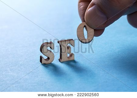 SEO from wooden letters on a blue background, a man's hand holds a letter O