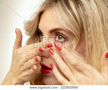 Transparent contact lens in the hands of a beautiful blonde who is preparing to insert it. Top view.