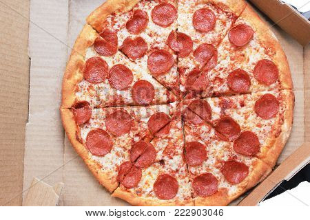 Pepperoni Pizza in Delivery Box Close Up Top View. Traditional Hot Italian Recipe Pizza with Pepperoni Sausage, Mozzarella Cheese and Tomato Sauce. Pizza in Card Paper Box Isolated on White Background