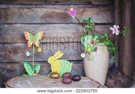 Easter composition of Easter eggs, a wriggle hazel with watering can, butterfly and heart and an artificial rabbot and flower with lady bug