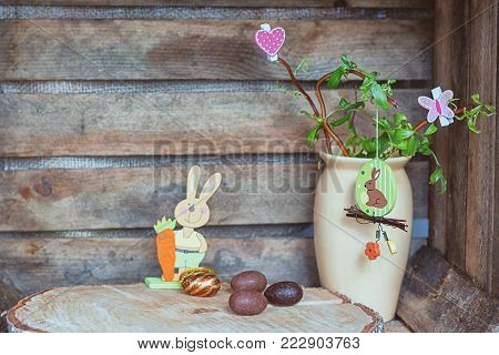 Easter composition of Easter eggs, a wriggle hazel with rabbit, butterfly and heart and an artificial rabbot with carrot