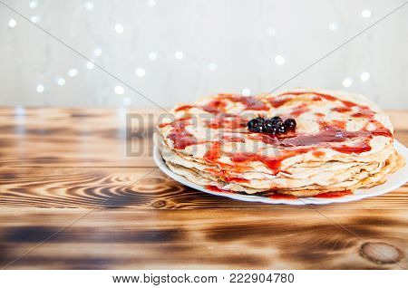Slapjacks with berries and jam on burnt boards