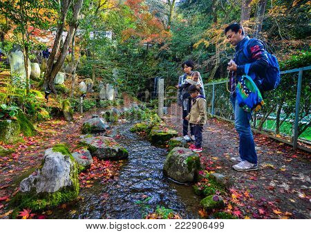 Kyoto, Japan - Nov 28, 2016. A family visit autumn park in Kyoto, Japan. Kyoto was the capital of Japan for over a millennium, and carries a reputation as its most beautiful city.