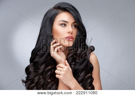 Beautiful Face of Young Woman with Clean healthy curly hair close up isolated on gray background. Beautiful Woman. Perfect Fresh Skin. Pure Beauty Model. Youth Skin and Hair Care Concept