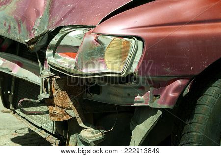 Damaged car. Front side of broken and damaged red car in car crash accident with fatal outcome in collision