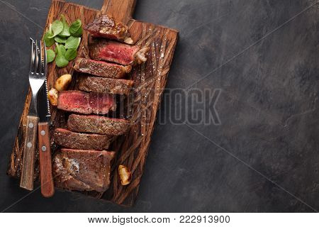 Closeup ready to eat steak new York beef breeds of black Angus with herbs, garlic and butter on a wooden Board. The finished dish for dinner on a dark stone background. Top view with copy space.