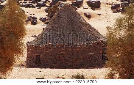 a traditional nomads hut built from stone and straw in the between two acacia tree on sand in west sahara in Mauritania