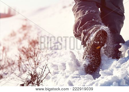 Person hiking on the mountaintop covered with snow low angle view. Man is doing outdoor activities. Supporting healthy lifestyle. Footprints on the snow.