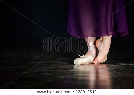 Elegant ballerina is posing in the studio on the dark background. She stands on the left toe and holds right leg on the floor. Girl wears one beige pointe shoe and long marsal satin skirt. Closeup. Horizontal. Her legs are reflected in the floor.