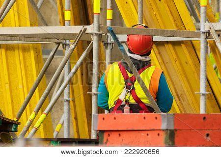 Worker in red helmet standing opposite of yellow scaffolding in reconstruction area