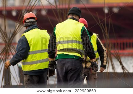 Three workers at the construction site work with armature