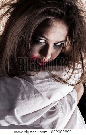 screaming crazy woman with fluffy hair in straitjacket looking at camera