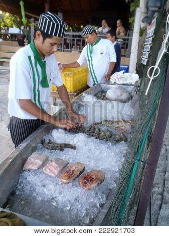 Koh Samui, Thailand April 28, 2013: a man is preparing the showcase of seafood of a restaurant on a beach in Koh Samui.