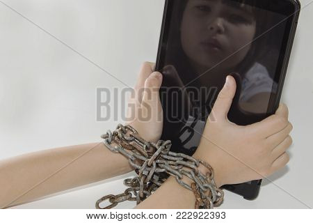 Iron chain ties together hands and smartphone - mobile phone addiction concept