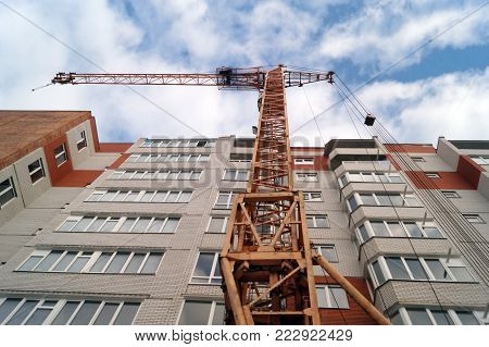 Facade of new multi-apartment high-rise apartment building. Construction of new modern multi-apartment residential complexes. Bottom view for new building and crane.