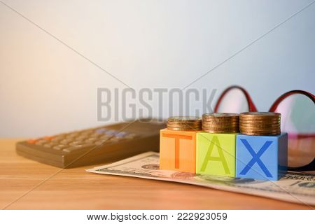Growing taxes - colour blocks with TAX and money stacks on table - Tax concept