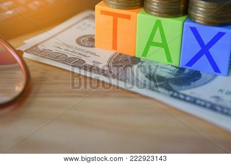 Growing taxes - Closeup of colour blocks with TAX and money stacks on table - Tax concept