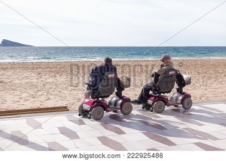 Benidorm, Spain - January 14, 2018: Seniors on mobility scooters looking to the sea in Benidorm, Spain.