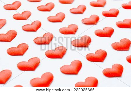 St Valentines day background. Red hearts on the white background, shallow DOF, Valentines day concept. Red silk hearts as symbols of St Valentines day. Festive St Valentines day background